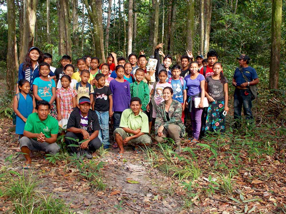 Four rows of people, many of them children, posing for a photo in a forest surrounded by tall trees