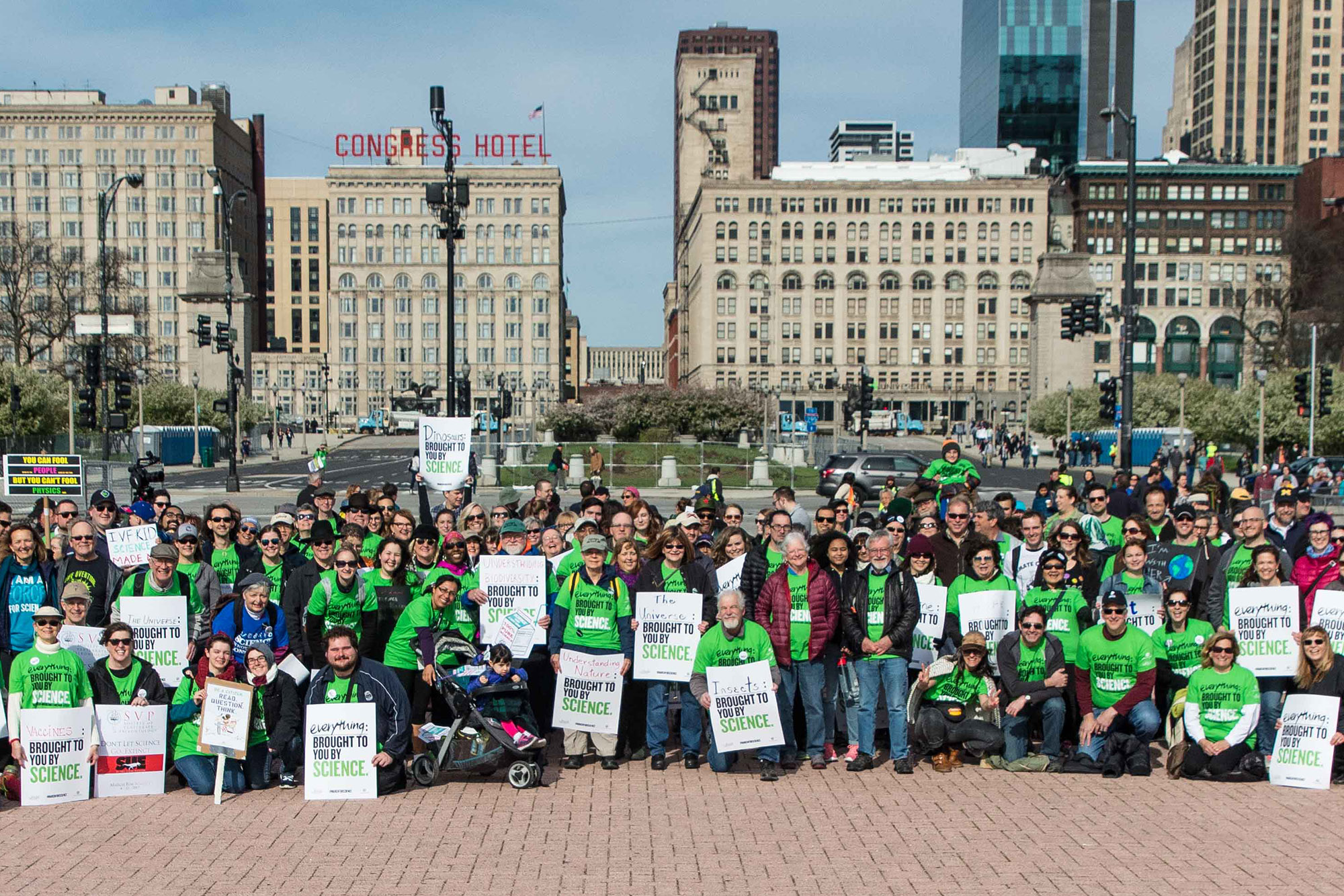 A large group of museum staff holding signs pose in Grant Park before the 2017 March for Science.