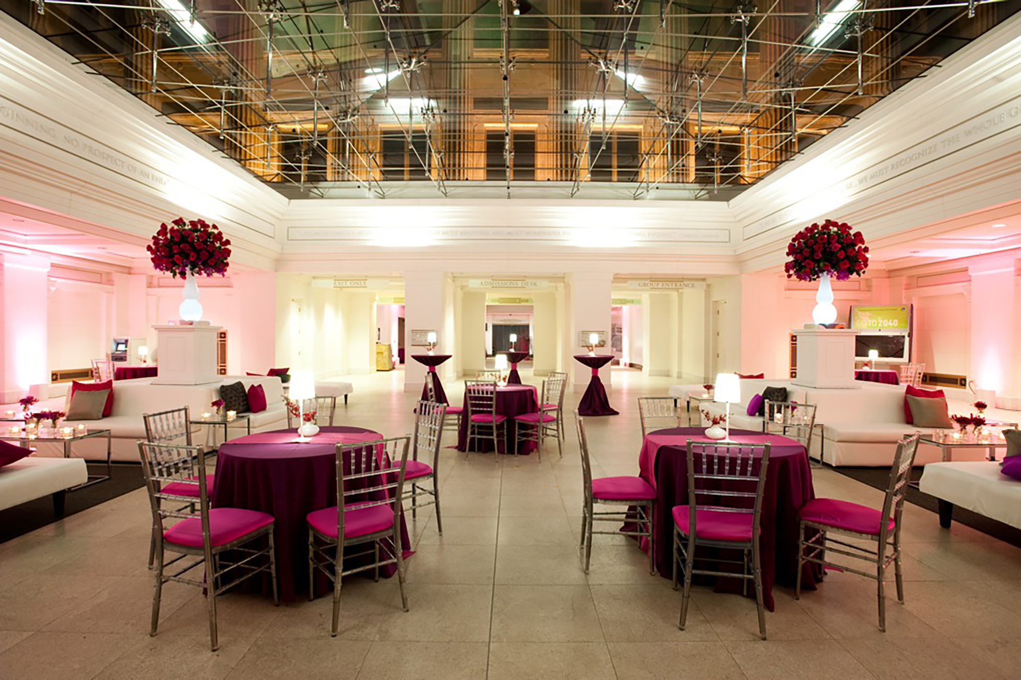 East Atrium space set up for an event with tall cocktail tables, small tables with five chairs eat, and white couches. Floral arrangements sit on while pillars behind the couches. A glass ceiling reveals the east facade of the Field Museum at night.