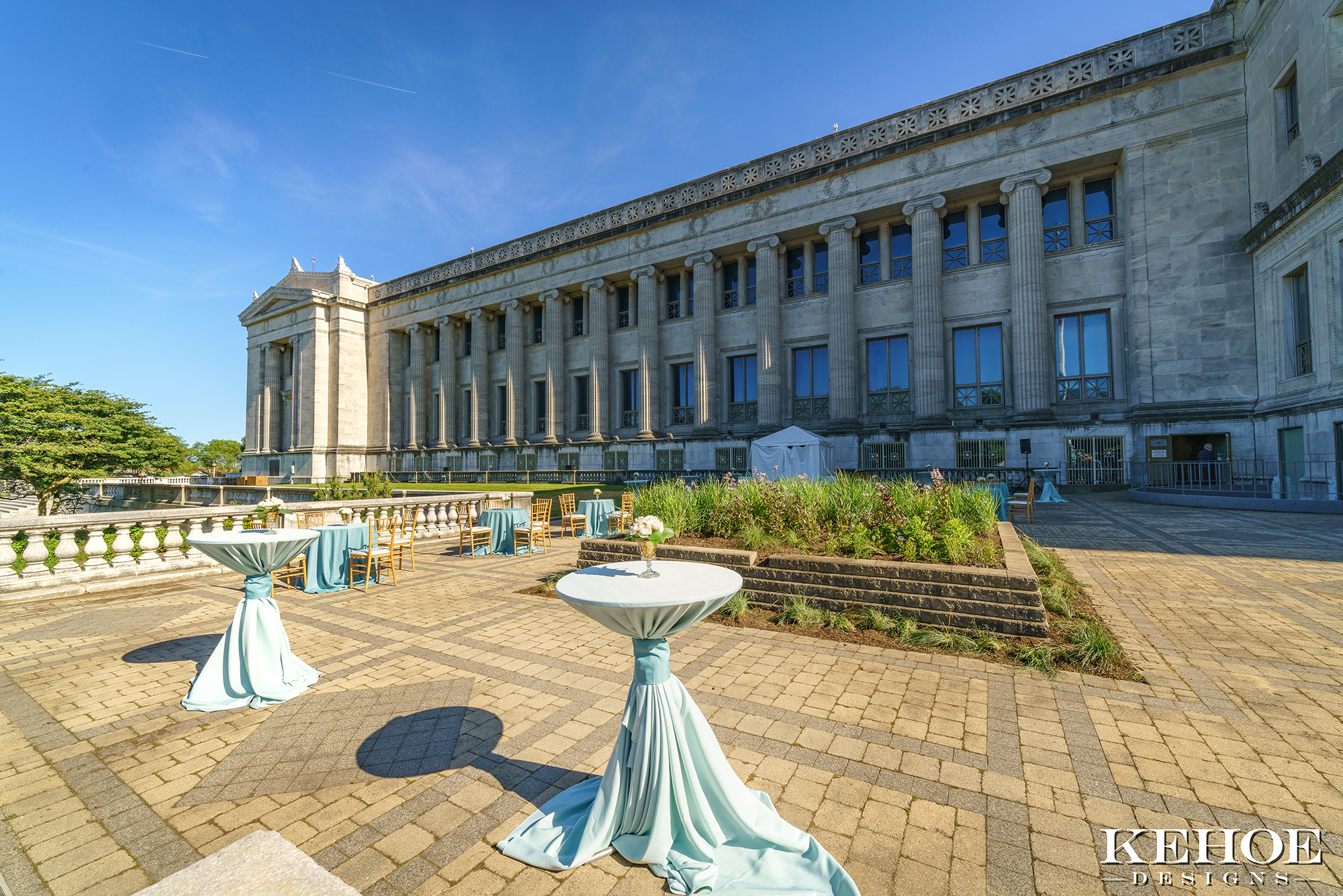 Cocktail tables arranged on the Field Museum's northeast terrace on a sunny day.