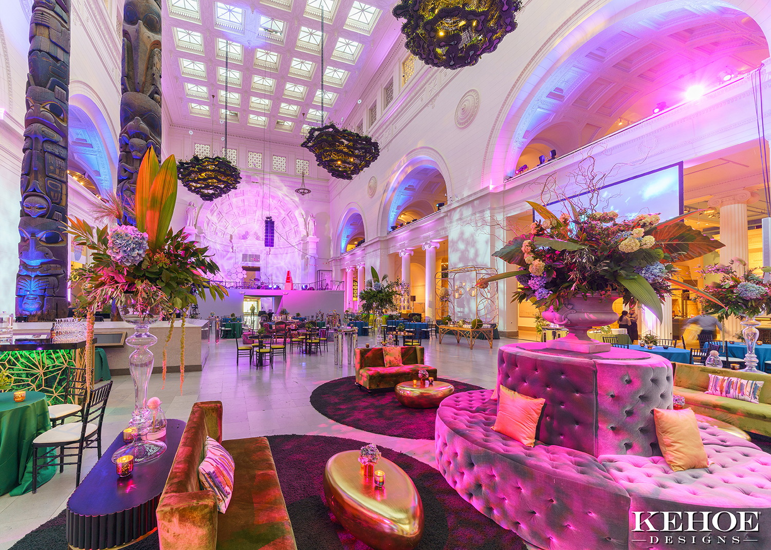 Warm, pink light fills Stanley Field Hall at the Field Museum, which is set up for an event with colorful tufted couches, rugs, and gold coffee tables. Floral arrangements decorate the space.
