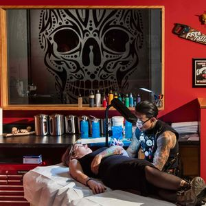 Tattoo artist Joel Molina tattoos a client in The Field Museum's tattoo shop