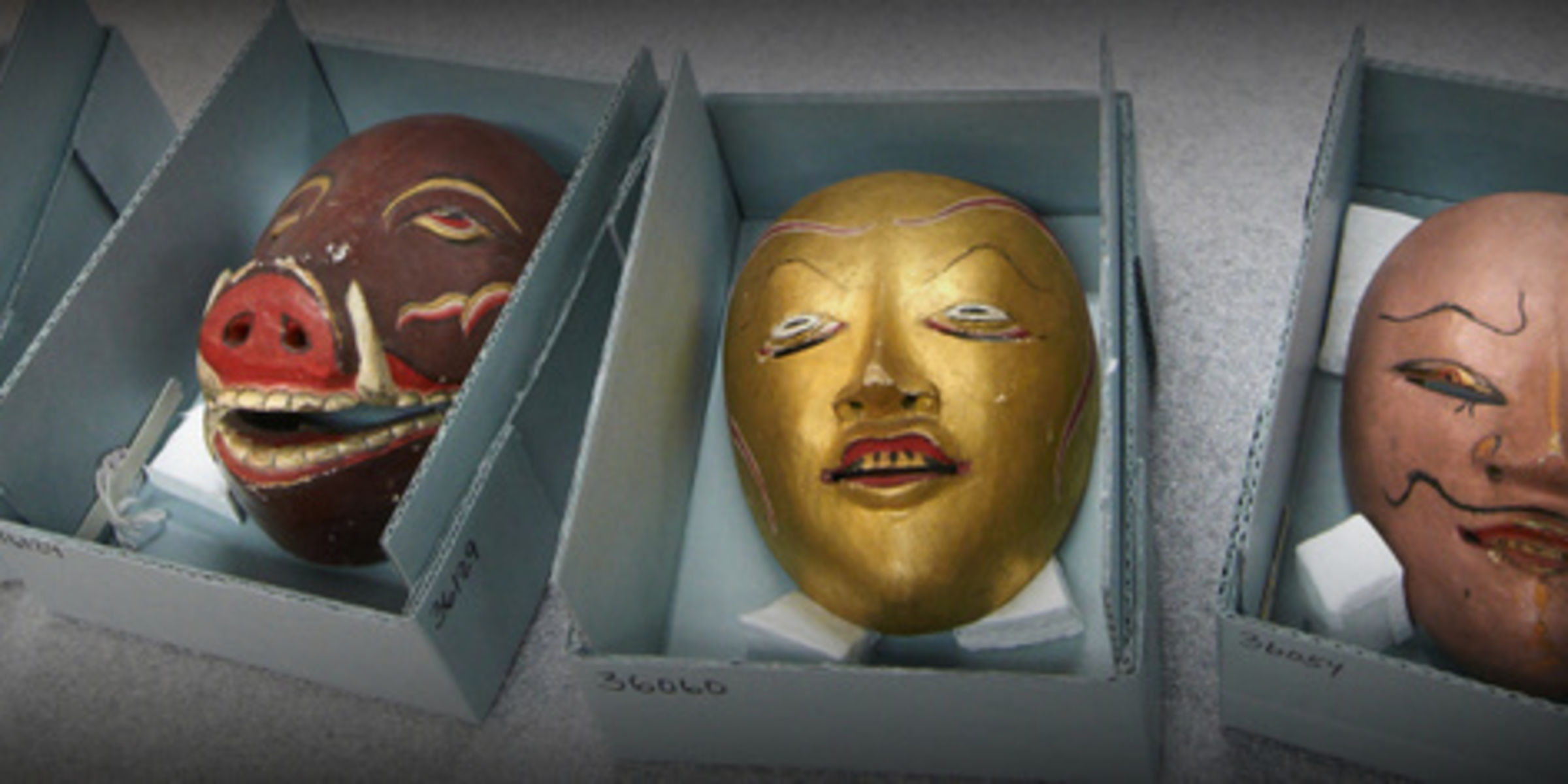 carved and painted masks in storage boxes
