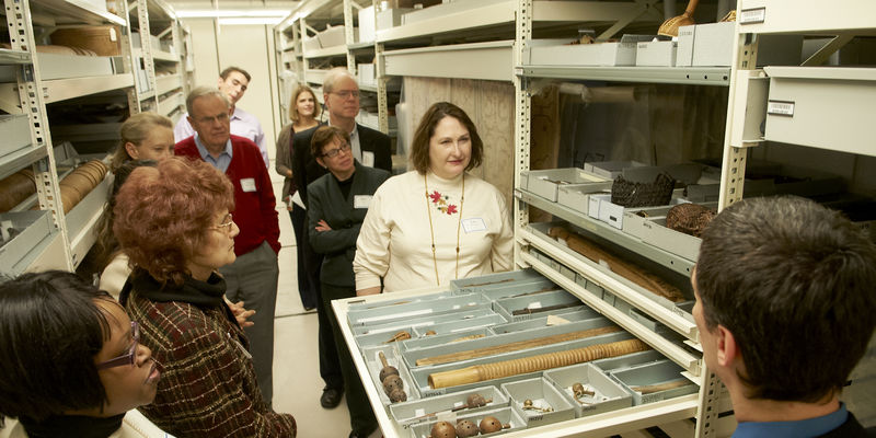 Group of people on a behind-the-scenes tour viewing objects on shelves