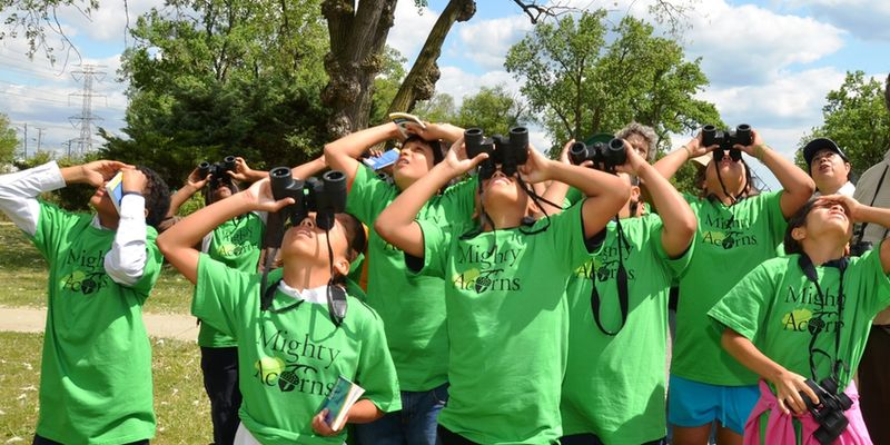 "A group of students in matching ""Mighty Acorns"" t-shirts use binoculars, looking upwards."