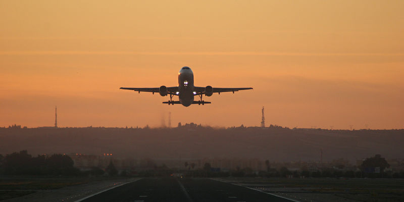 A plane taking off from a runway in front of an orange sky