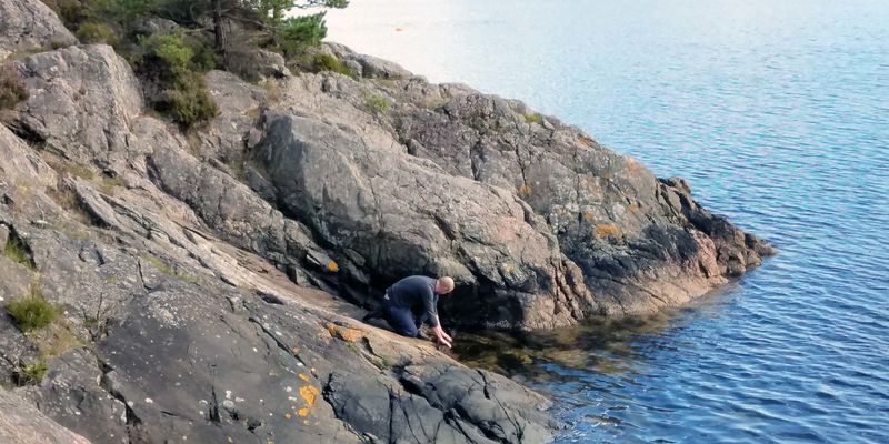 A man looking for something on a rocky coast next to bright blue water