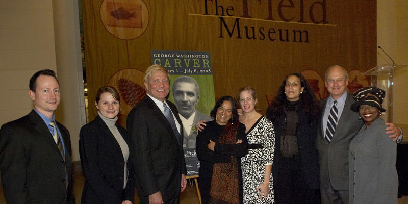 Field Museum staff members and supporters pose together near a sign promoting the George Washington Carver exhibition at an opening event.