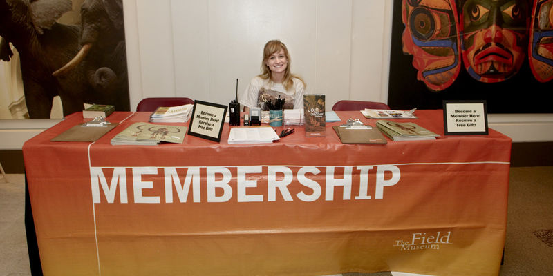 "A female employee of The Field Museum sits behind a table decorated with a ""Membership"" banner."