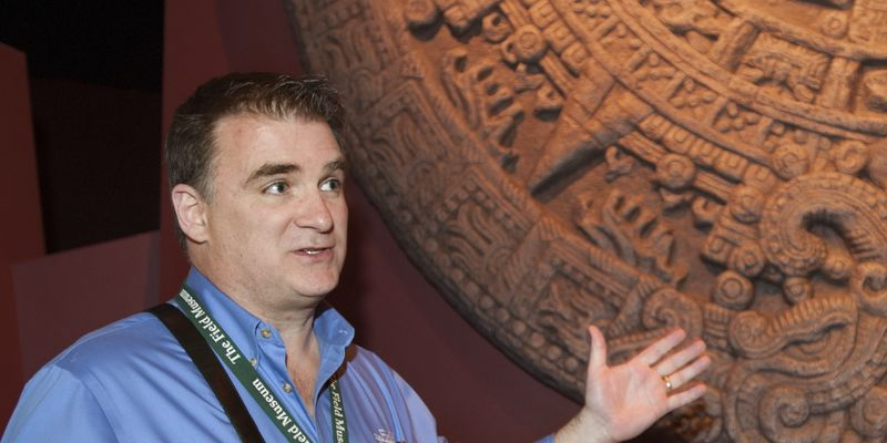 A male docent gestures towards an Aztec item in the Ancient Americas exhibition.
