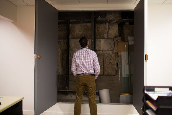 Man standing in an office front of two open doors cut into the wall. They reveal the stone walls of an Egyptian tomb.