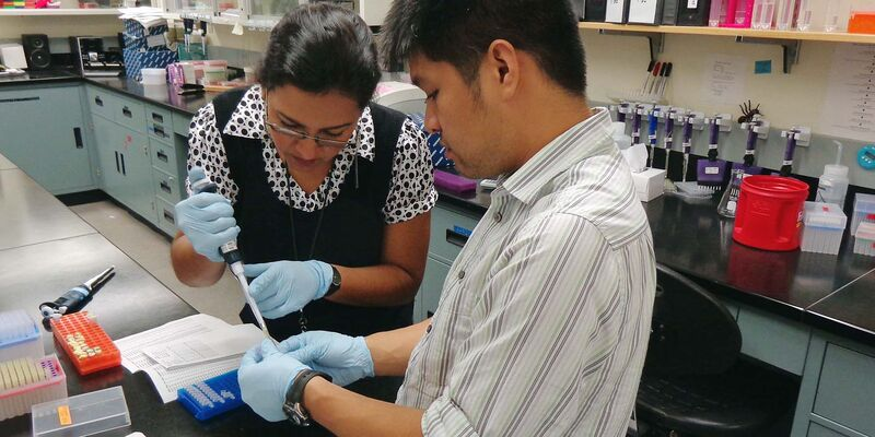 A woman and a man in a lab using a pipette