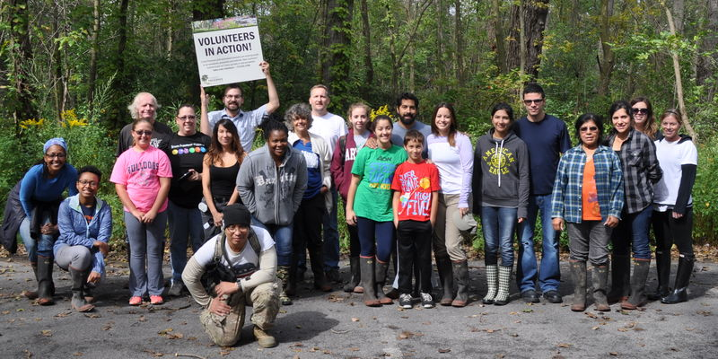 "Habitat restoration volunteers of all ages gather for a photo in a wooded area. One person holds up a ""Volunteers in Action"" sign."