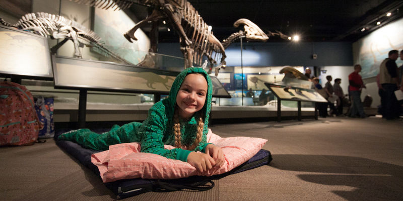 Young girl in pajamas lying on sleeping bag in Dinosaur Hall