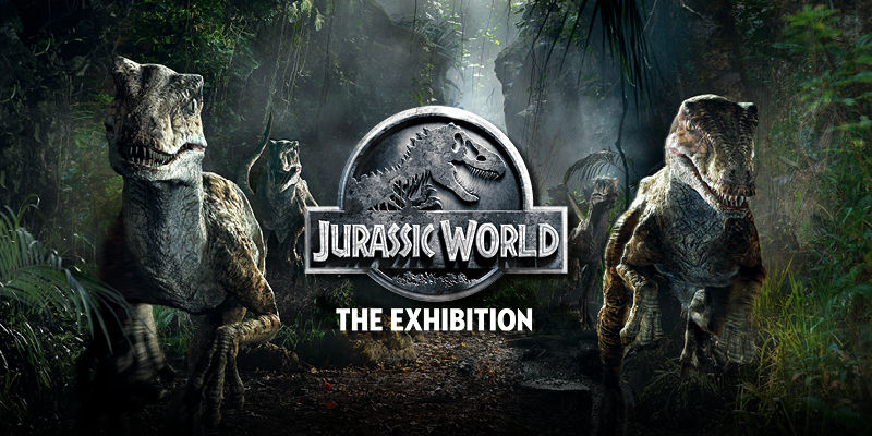 Logo for Jurassic World: The Exhibition set on a jungle-like background with two raptors on each side.