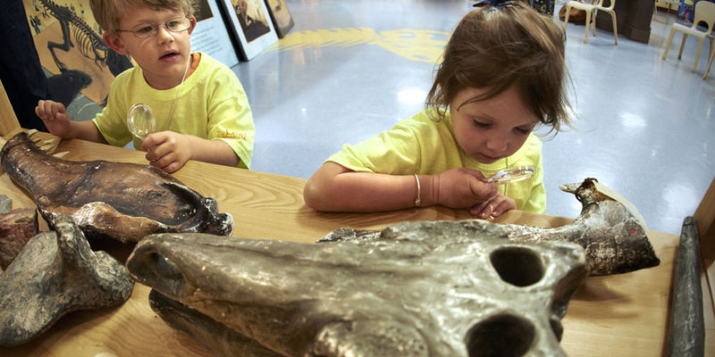A boy and a girl use magnifying glasses to take a closer look in the Crown Family PlayLab