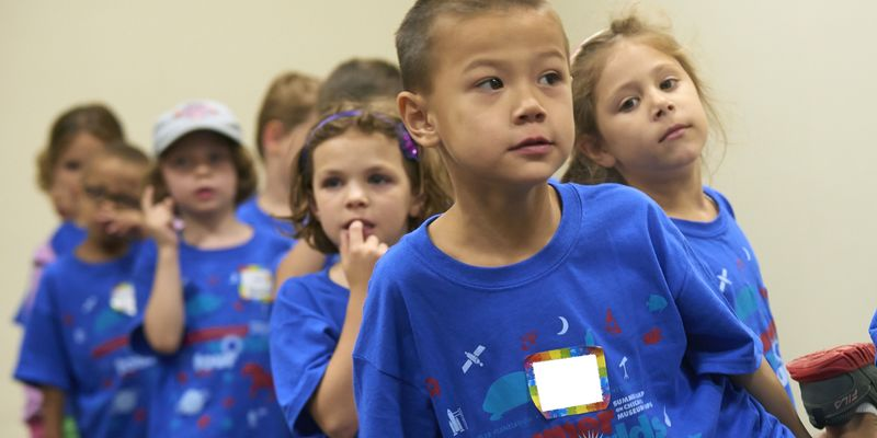 "Group of pre-school age campers line up in matching ""Summer Worlds Tour"" t-shirts."