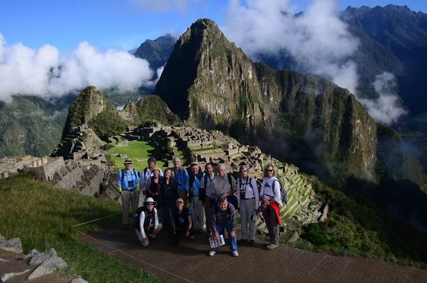 Tour group led by Field Museum scientist poses at Machu Picchu with view of the Inca city behind them.