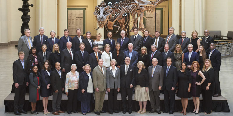 Trustees pose in front of SUE the T. rex.