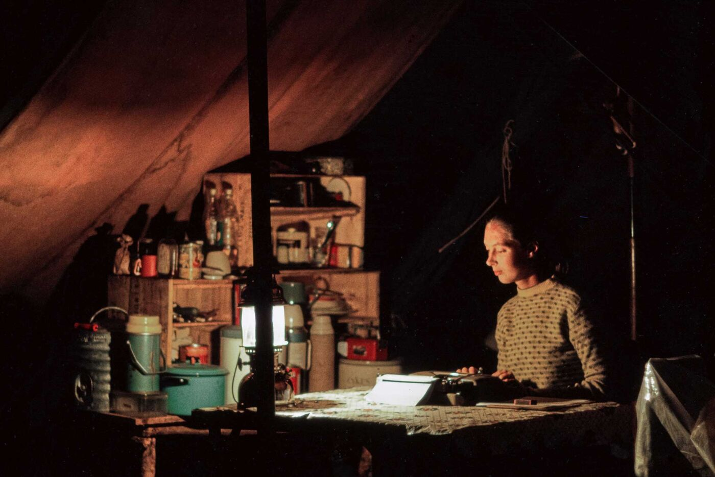 Jane Goodall in a field tent using a typewriter by the light of a lantern.