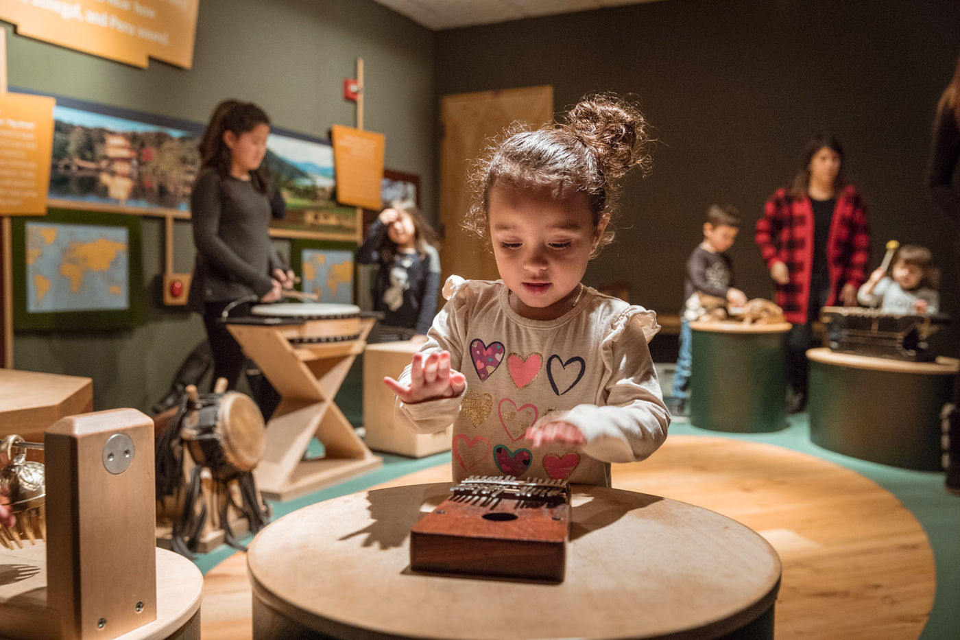 A child plays a mbira in the foreground, while behind her other children play drums and a xylophone.