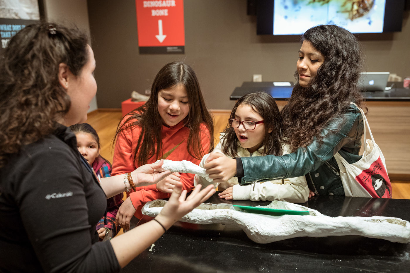 A woman and three children gather around an educator holding a specimen. Group members reach towards the specimen.