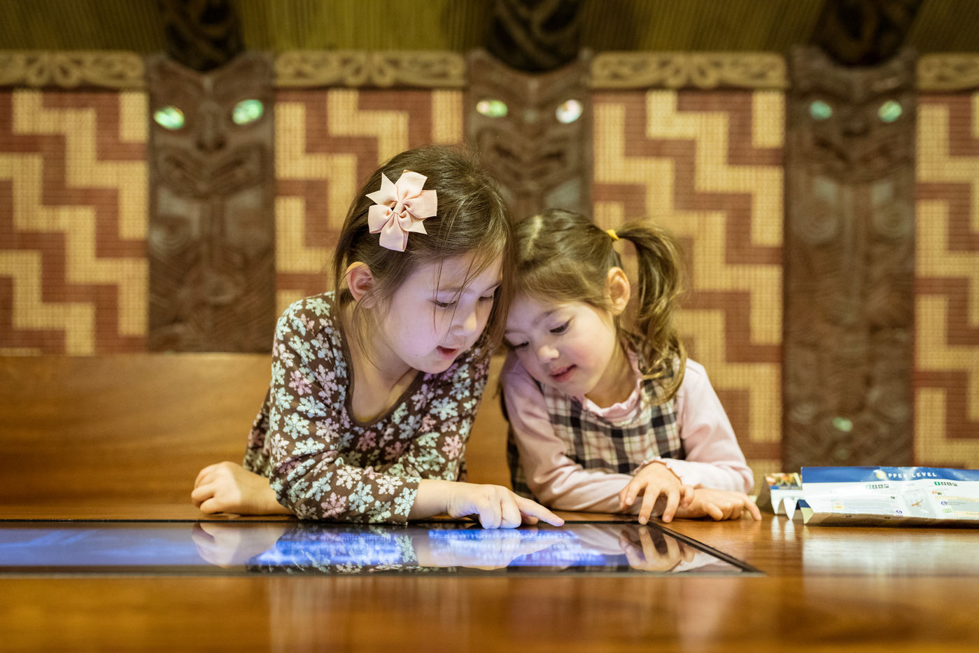 Two young girls stand close together around a touchscreen set into a wood table on the left side of the Maori meeting house.