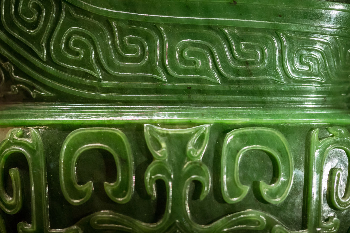 Close-up view of a jade vessel carved with repeating spiral and curvilinear patterns.