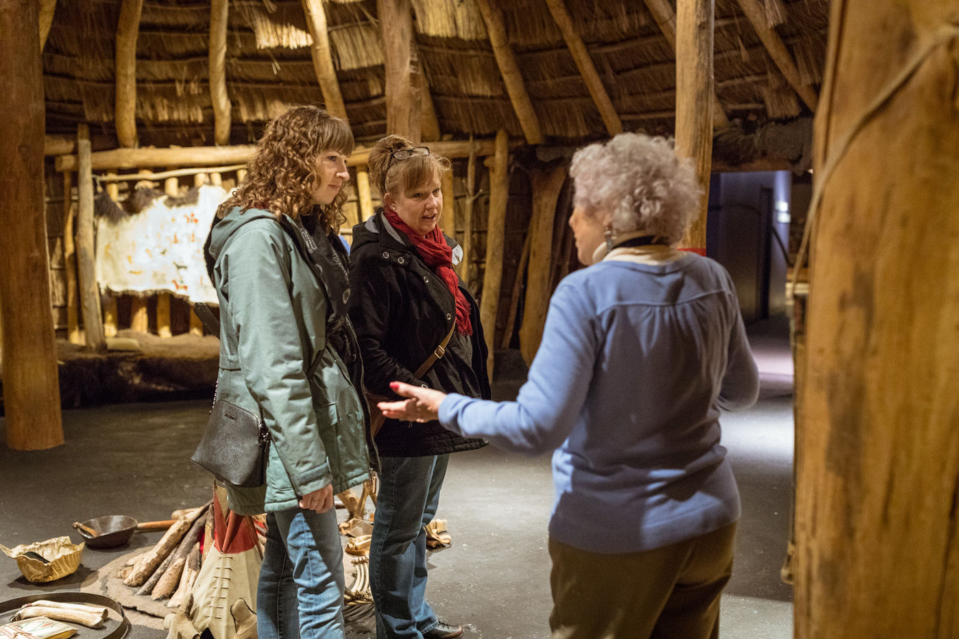 A museum docent talks to two visitors inside the Pawnee Earth Lodge.