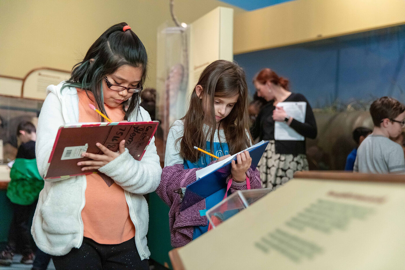 Two students write on clipboards while touring the Field Museum.