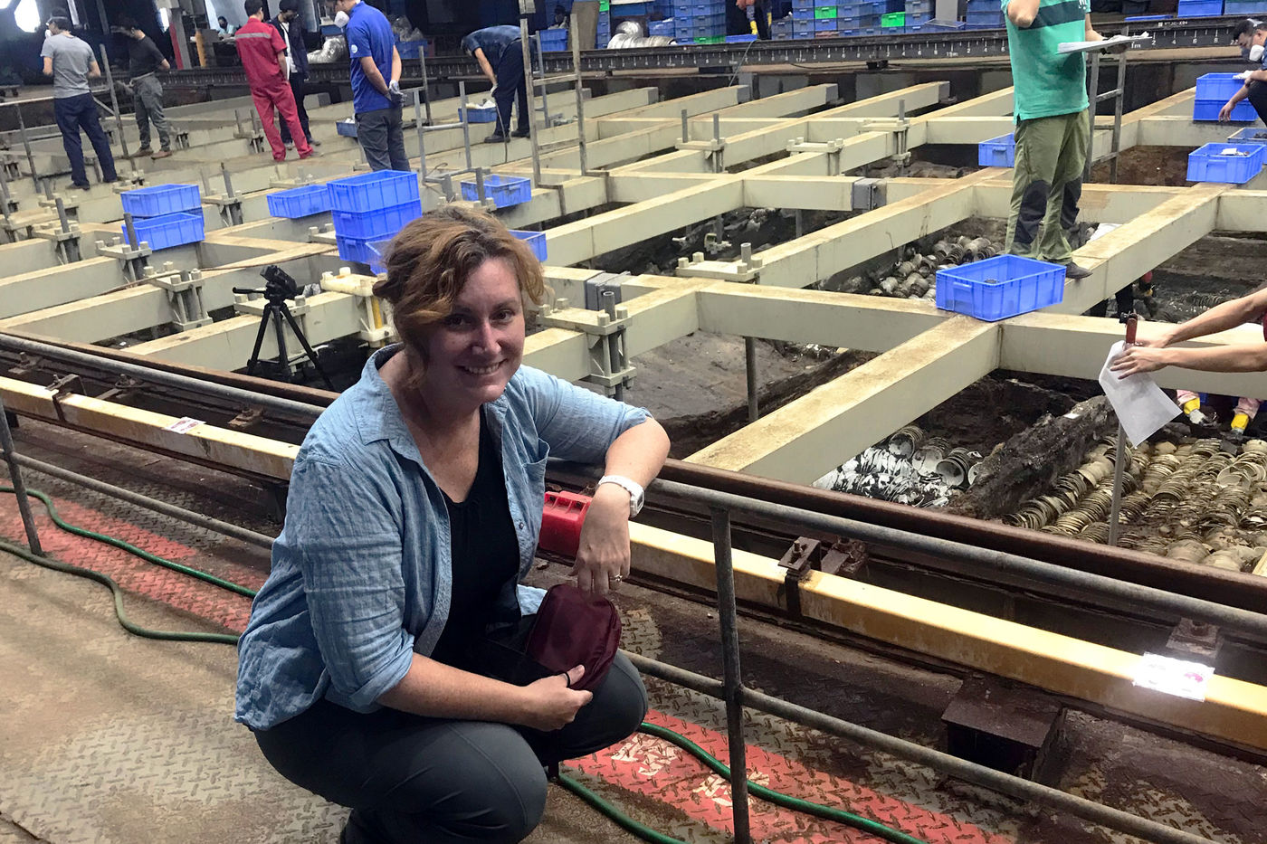 A woman poses in front of a large excavation site, where workers stand on a grid system of beams over the remains of a shipwreck. The nearest quadrants contain tightly stacked bowls.
