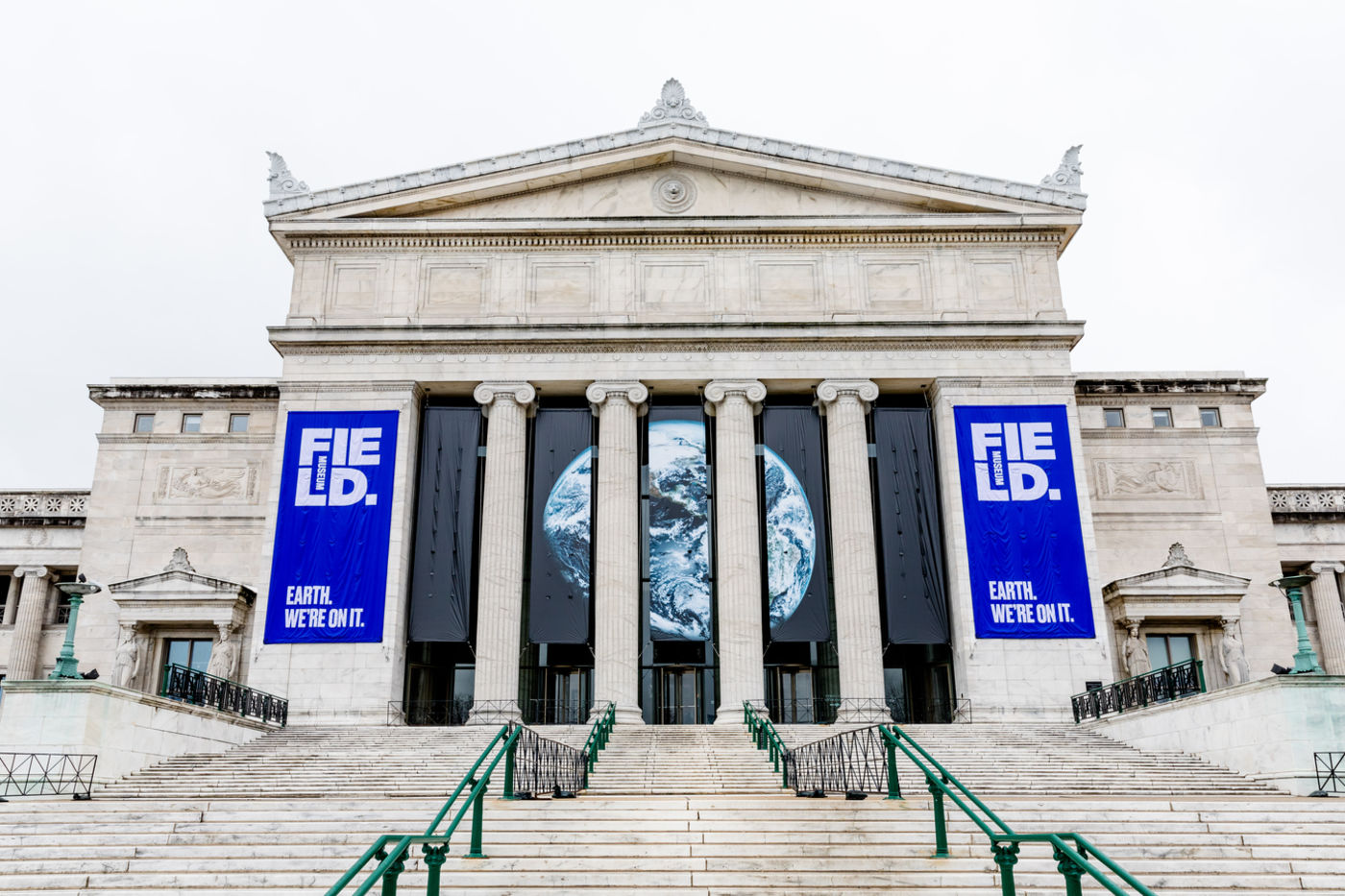 "Looking up at the North facade of the Field Museum from the bottom of its long front staircase. Two blue banners with the Field Museum's logo read, ""Earth. We're on it."" and frame a large satellite image of Earth from space on a black background."