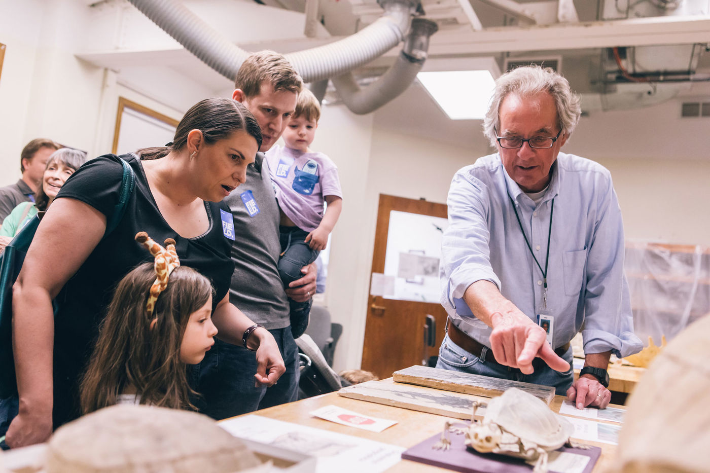 Two adults and two children listen to a staff member, who points to a specimen on display at Members' Nights.