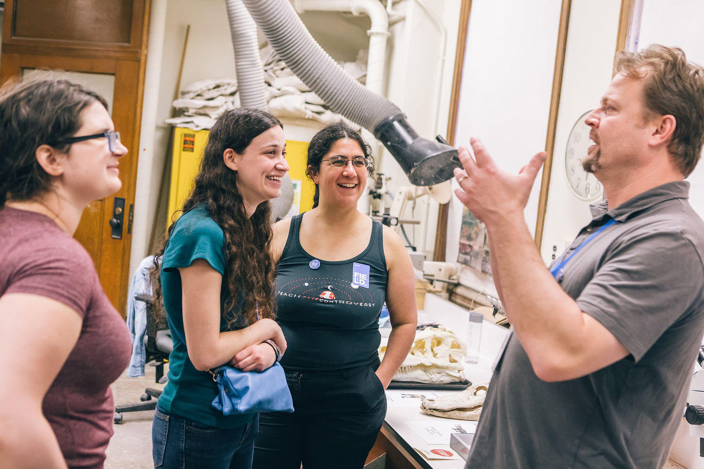 A group of four people stand and talk in a lab. They're gathered around a table that displays several fossil specimens. Cabinets, a ventilation duct, and door are visible in the background.