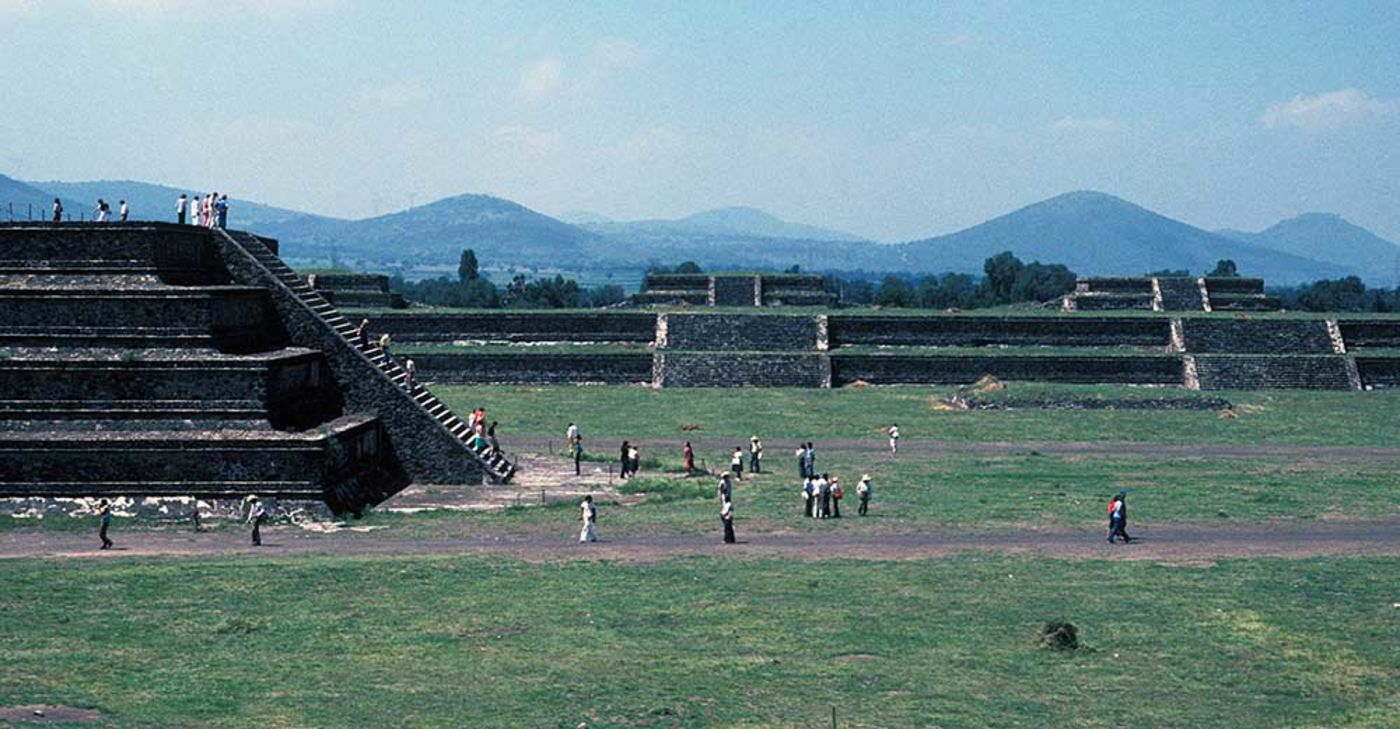 A large open square surrounded by city ruins, including a stone structure with stairs that people are climbing