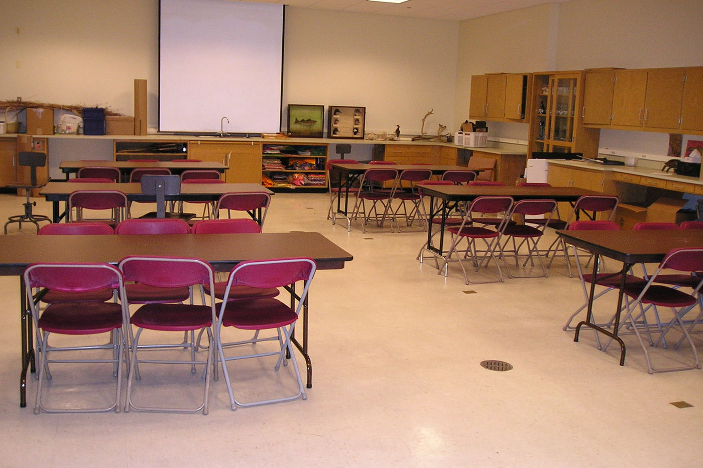 A view of Classroom B. Six desks are arranged in two rows, facing a projector on the wall in the front of the room. Each table seats six guests. Counters and cabinets line the walls of the room.