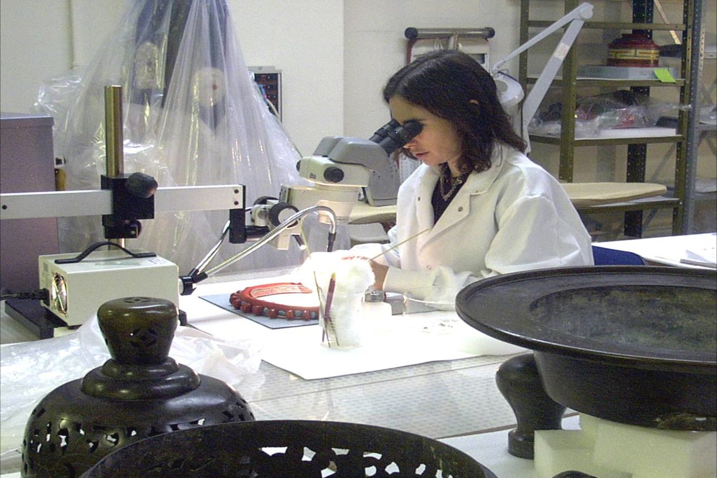 Museum conservator uses a microscope to examine an object