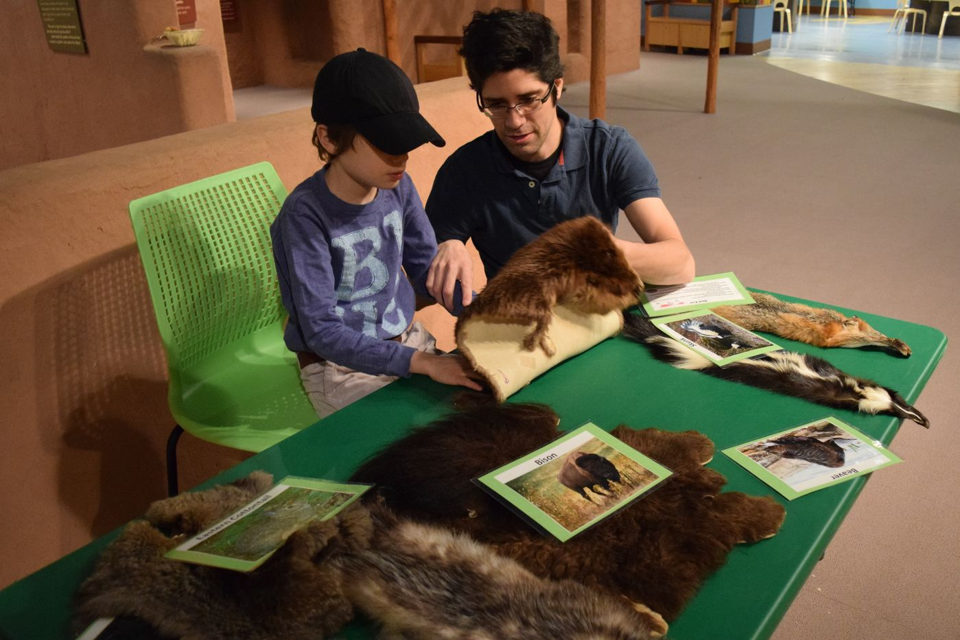 Caregiver and child sit a table in front a replica pueblo in the Crown Family PlayLab. Together, they study an animal pelt.