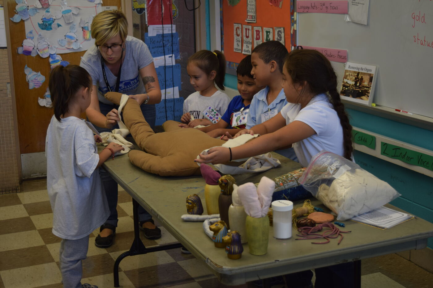 Park Voyagers instructor showing students a model of a mummy