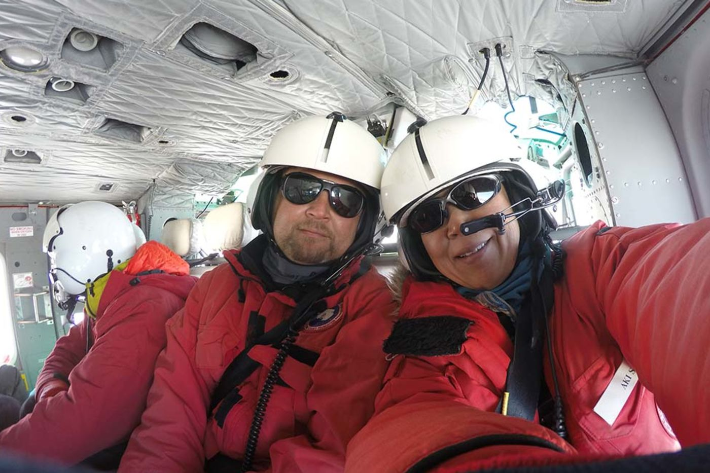 A man and a woman in red suits, white helmets, and sunglasses aboard a helicopter.