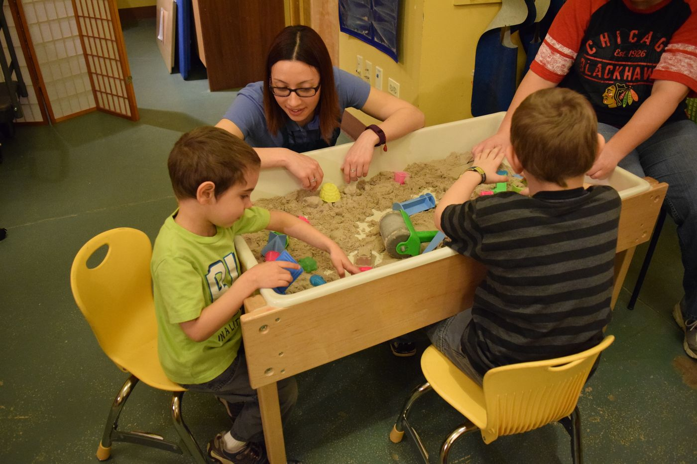 Two children sit around a sandbox, using molds to make shapes. An adult crouches down to their level.