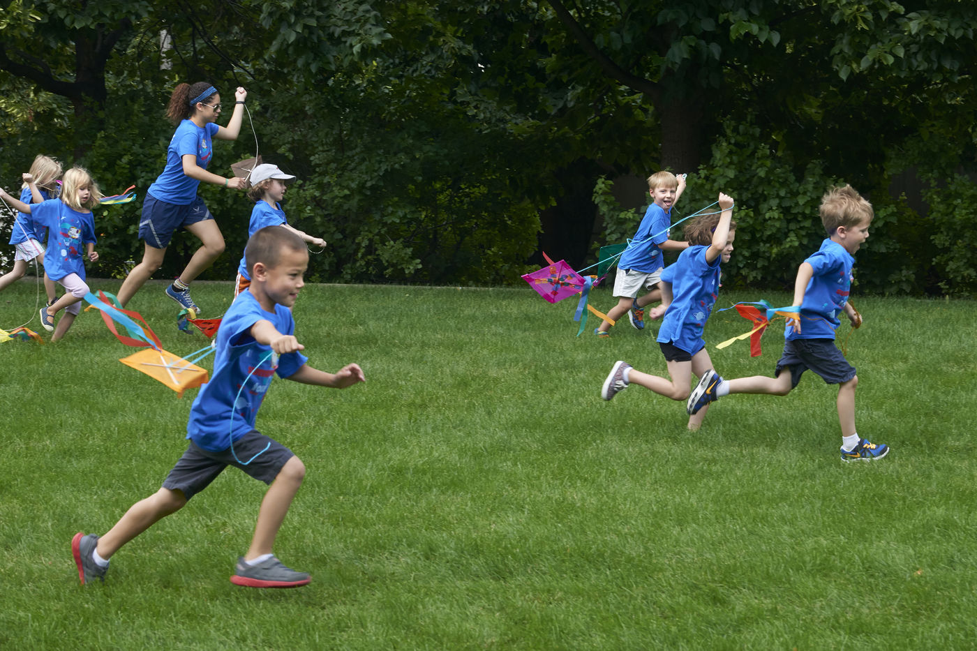 Children, accompanied by a counselor, race through the grass on the Museum Campus pulling kites along.