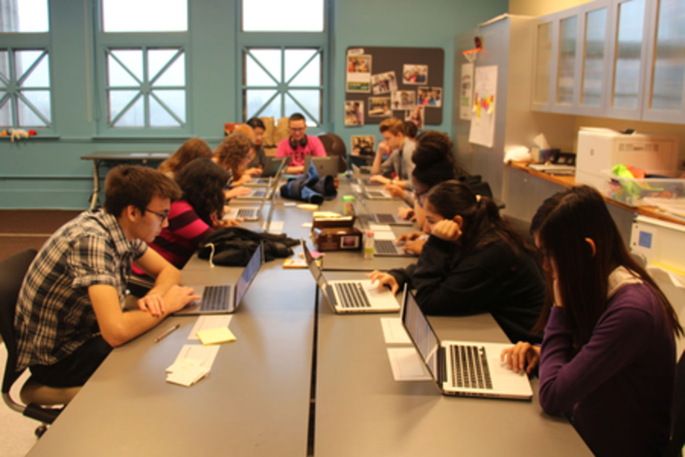 Two rows of teens sit at a long, gray table in a room with three large windows against the back wall. Each teen is looking at their own laptop computer.