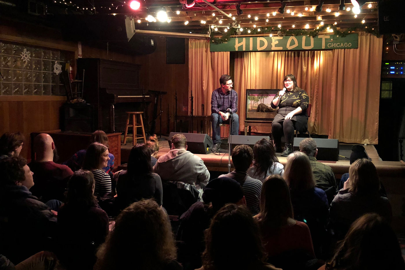 """A man and woman sitting on a small stage speak to a crowd that is seated in front of them. A sign reading, """"The Hideout Chicago"""" hangs behind them. The woman holds a microphone, and the man looks towards her."""