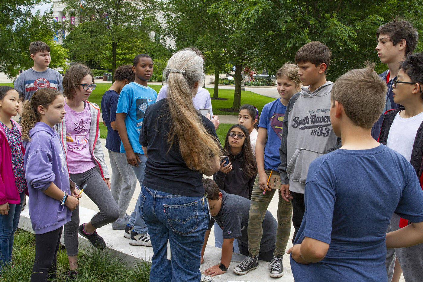A group of Tween Camp participants gather outside to listen to a woman speak. The women's face is not visible. Some participants stand behind her on grass. Others stand in front of her on a sidewalk.