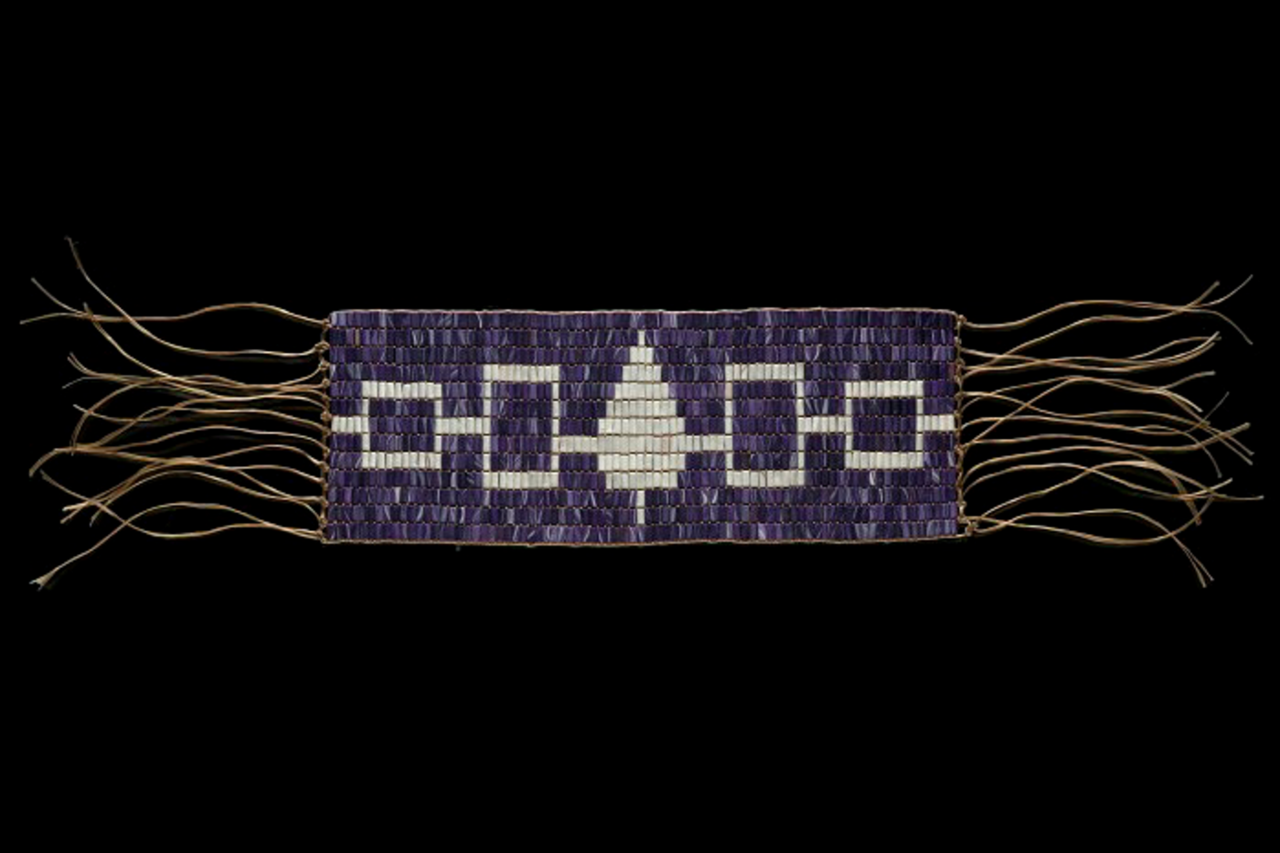 A purple and white beaded wampum belt.