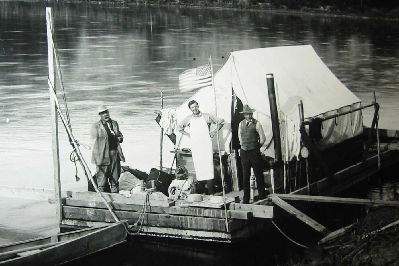 Three men, one wearing an apron, stand on a floating platform that's anchored to land. A tent and an American flag are affixed to the barge.