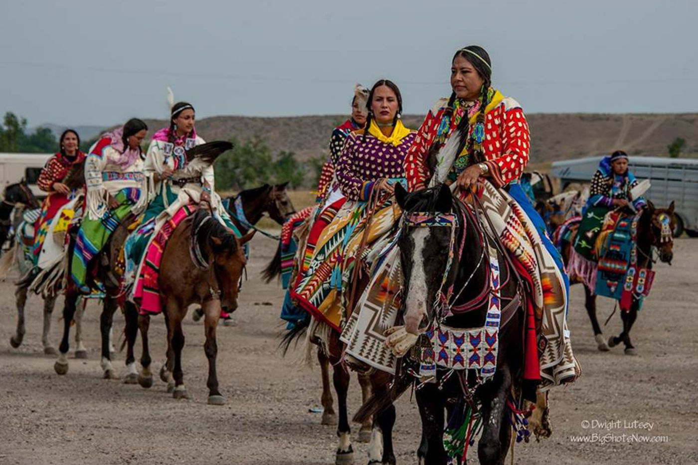 A group of Apsáalooke women on horseback, wearing traditional clothing and accessories.