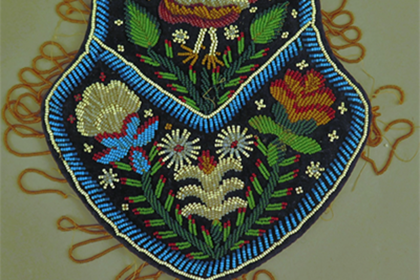 Brightly colored beaded purse depicting a bird and flowers