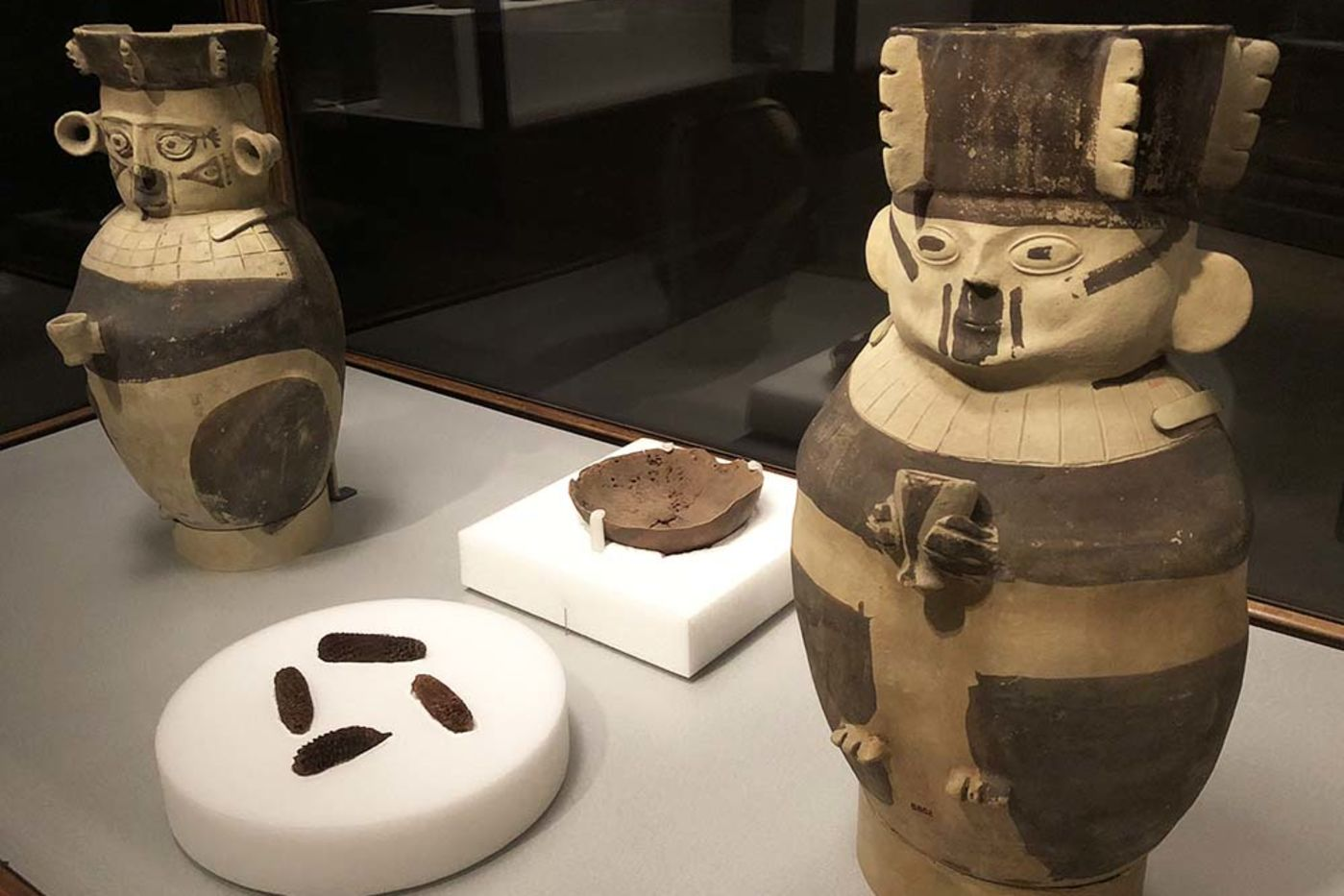 Two ceramic jugs in the shape of human figures holding small cups, painted with dark brown accents